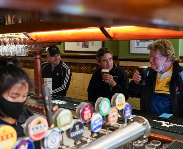 From left: customers Brian O'Mara, Darrell Forman and Doug Thomas share a beer together at the...