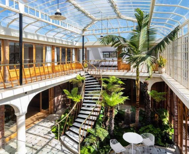 Spectacular glass conservatory and curved marble staircase. Photo: Supplied