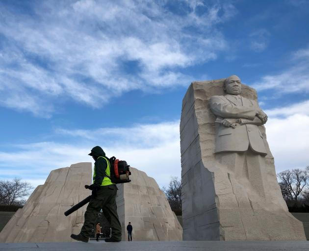 A man cleans debris around the Martin Luther King Jr Memorial in Washington, one of 800,000...