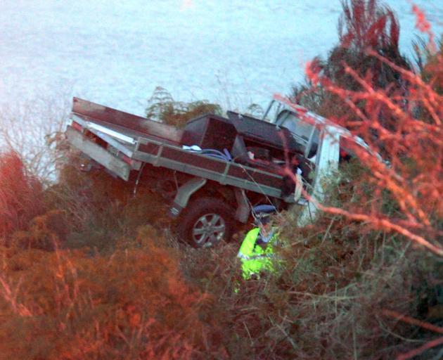 An officer checks a ute that crashed on railway tracks next to Blueskin Bay near Waitati this...