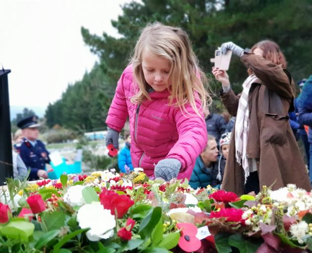Mikayla Clark (7), of Lake Hawea, lays a poppy on the Hawea Memorial at her first dawn service....