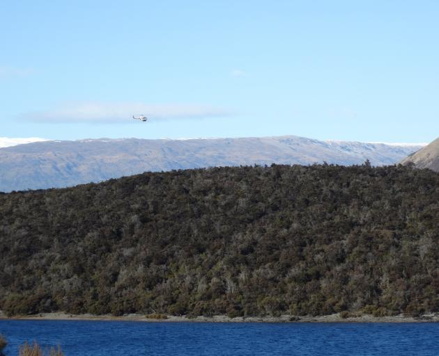 A helicopter searches over Lake Wanaka for the missing helicopter pilot. Photo: Sean Nugent