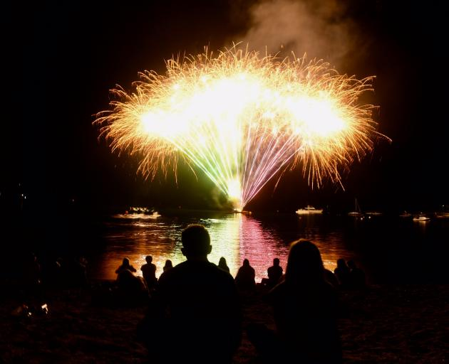 New Year's revellers watch a fireworks display from the Wanaka lakefront. Photo: Stephen Jaquiery