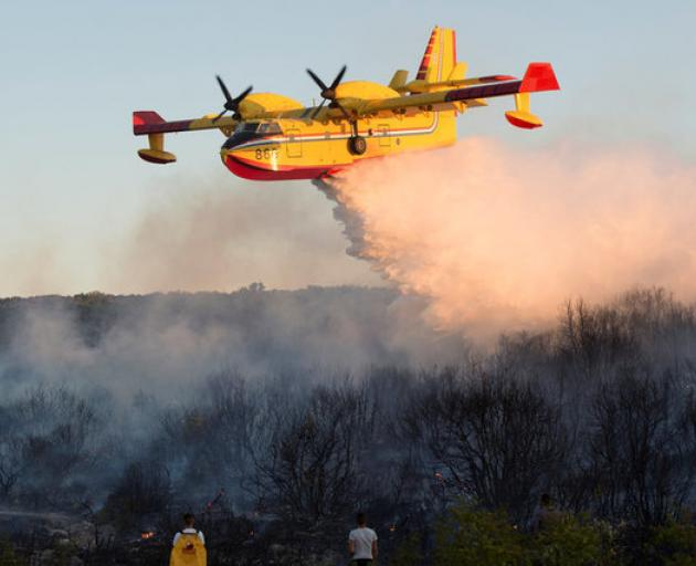 A firefighting plane drops water to extinguish a forest fire near Zadar, Croatia. Photo: Reuters