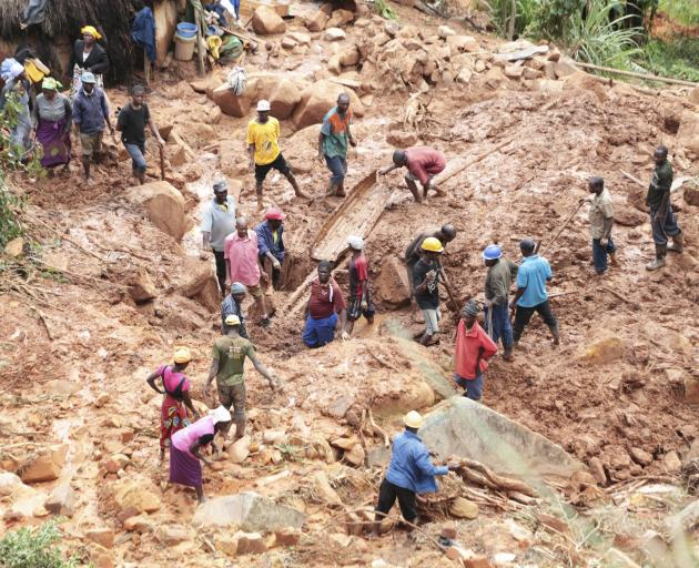 A family dig for their son who got buried in mud when the cyclone struck Chimanimani in Zimbabwe....