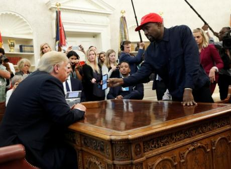 Rapper Kanye West shows President Trump his mobile phone during meeting in the Oval Office. Photo...