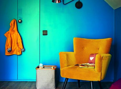 A wall of built-in storage in this children's room has been painted a rich teal blue, while the...