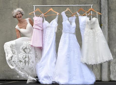 St John Dunedin Store staff member Pauline Bell models one of the brand-new wedding dresses which...