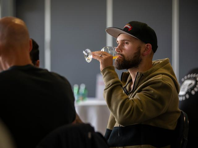 Mason Pratt, Emerson's senior brewer, blind taste tests an entry during the awards' judging.