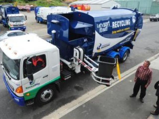 Dunedin city councillors Lee Vandervis (left) and Andrew Noone watch one of Dunedin's new refuse-collection trucks scoop up a 240-litre wheelie bin during a demonstration yesterday. Photo by Craig Baxter.