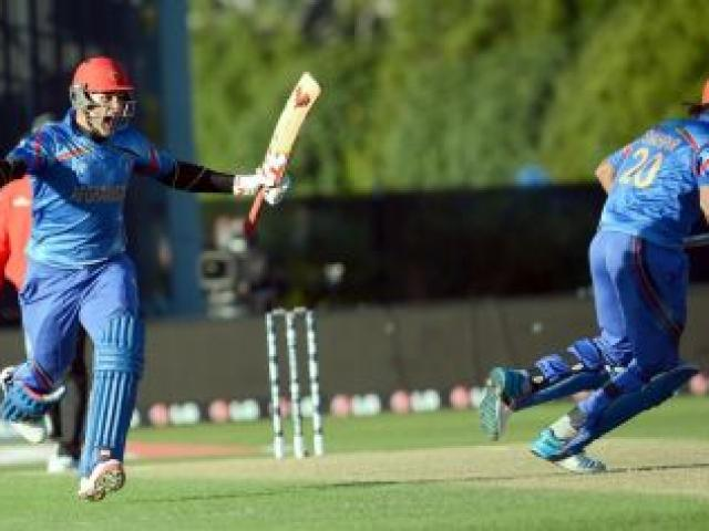 Afghanistan's Hamid Hassan (left) celebrates while Shapoor Zadran sets off on a victory dash after hitting the winning runs to seal a dramatic World Cup win against Scotland at the University Oval yesterday. Photo by Peter McIntosh.