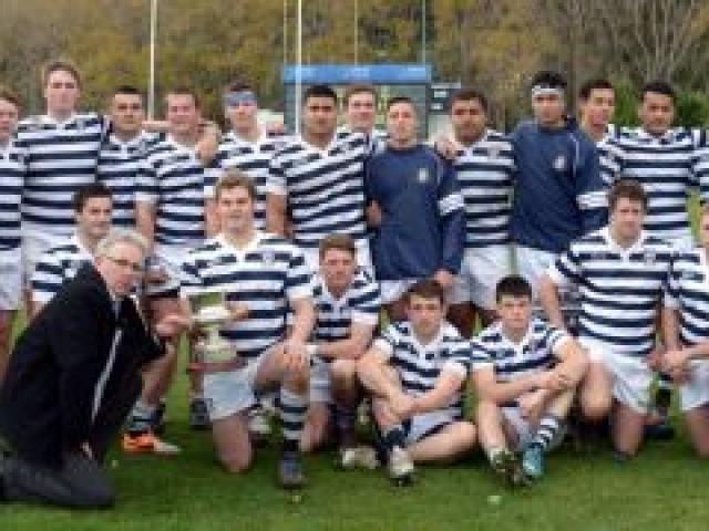 Allied Press group advertising manager Paul Dwyer congratulates the Otago Boys' High School First XV on winning the ODT Cup on Saturday, topping its pool in the Highlanders First XV competition. King's High School won the Express-Ensign Cup for winning th