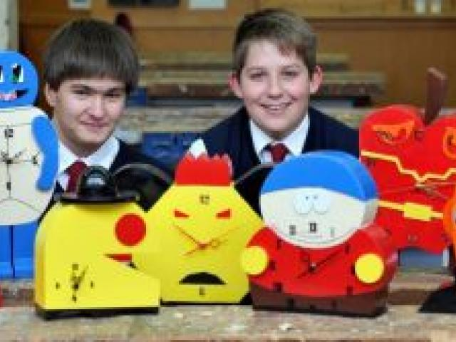 Kavanagh College pupils (from left) Shaun Tatley, Taylor Pearce and Tomas Woodford-Webb (all 15) with some of the cartoon clocks created during their hard materials technology class. Photo by Craig Baxter.