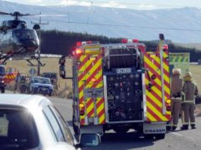 Emergency services at the scene of a car crash yesterday near Clarks Junction on State Highway 87. The sole occupant received a serious head injury.  Photo by Craig Baxter.