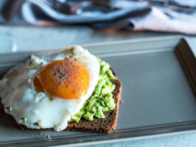 Grainy toast and avocado topped with an egg. Photo: Getty Images