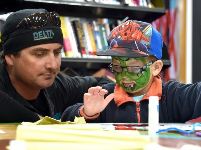 Craig Booth guides his son Harrison (4) as he gets creative with art supplies  at the Storylines...