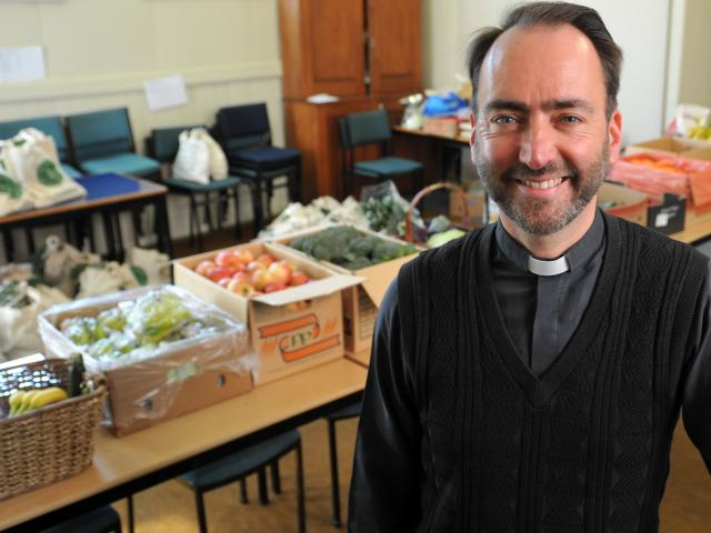 The Rev Michael Wallace relaxs after packing fruit and vegetables into bags for the All Saints' fruit and veges co-operative scheme. Photos by Christine O'Connor.