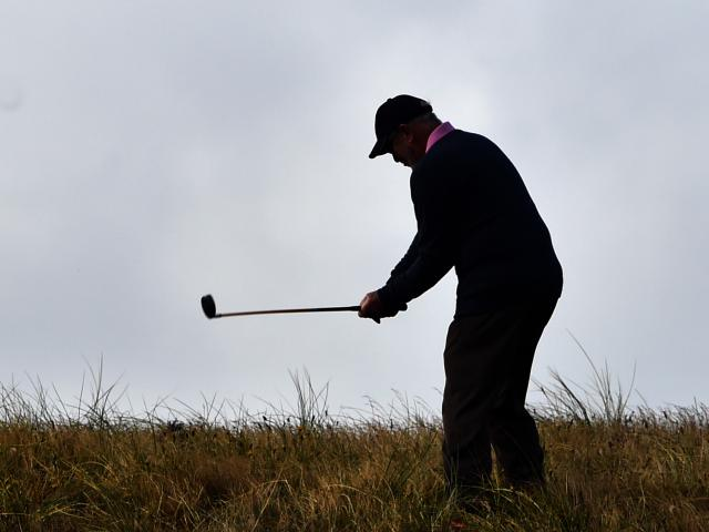 Peter Robson, of Brisbane, plays a chip shot on the ninth hole during the national left-handed...
