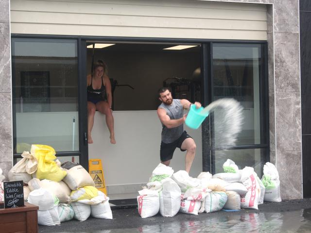 FIT FX gym owner Marty Greaney throws a bucket of water out of the gym after about 8cm of...