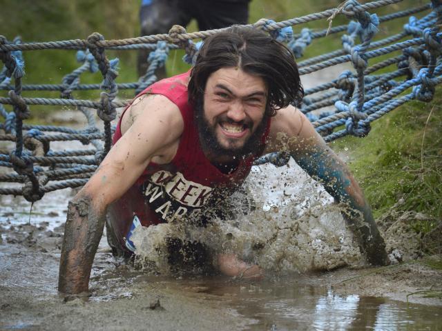 Mud, Sweat and Tears men's 10km winner Jonah Smith, of Dunedin, crawls through a muddy ditch....