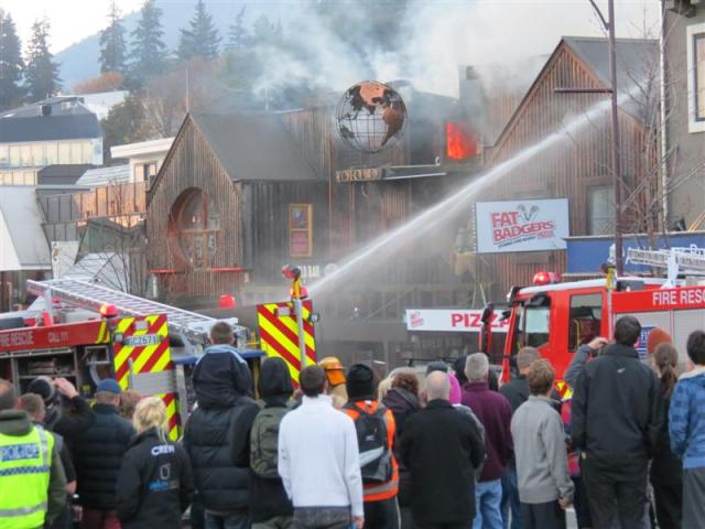 Firefighters battle the blaze in the building that houses the World Bar, Fat Badgers Pizza and...
