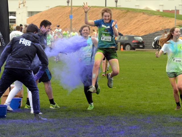 Clora Quinlan-Thompson (16) jumps through a cloud of coloured corn starch, flanked by Kate...
