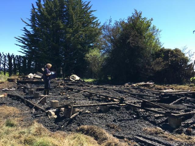 A firefighter examines the remains of the old church destroyed by a fire in Riverton. Photo: Ruby...