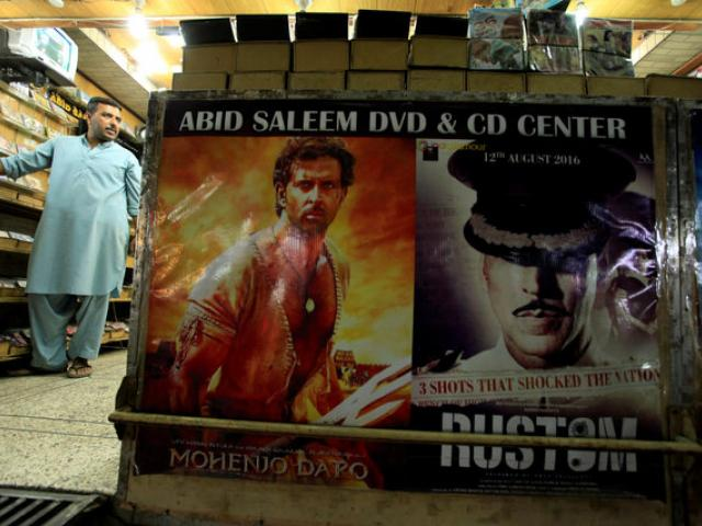 A man stands in a DVD shop displaying posters of Bollywood movies in Rawalpindi, Pakistan. Photo:...
