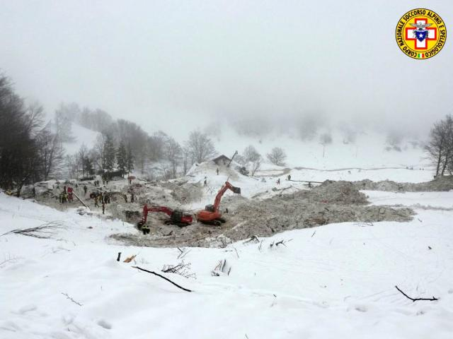 Rescue workers work with an excavator at the site of the avalanche-buried Hotel Rigopiano in...