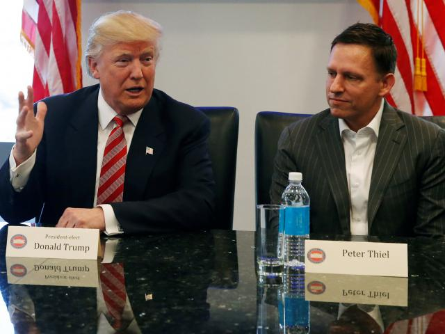 US President Donald Trump sits with PayPal co-founder and Facebook board member Peter Thiel,...