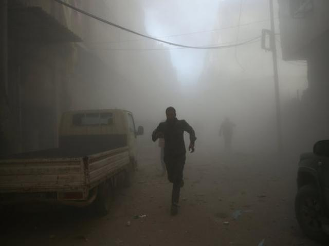 Men run at a site hit by airstrikes in the rebel held besieged Douma neighbourhood of Damascus....