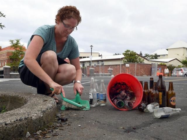 Kimberley Smith, of Dunedin, sweeps up other people's broken glass after becoming sick of having...