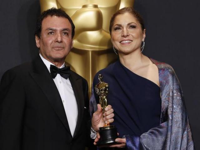 Anousheh Ansari and Firouz Naderi pose with the Oscar they accepted on behalf of Asghar Farhadi....