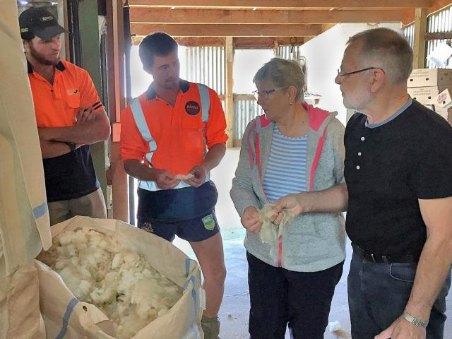 Landcorp employees Peter O'Malley (left) and Mace Lee, from Waipori Station, talk wool with Nanny...