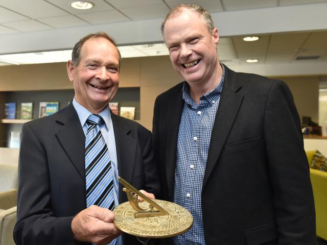 Retiring TracMap chairman Pat Garden (left) with the sundial he received as a retirement gift,...
