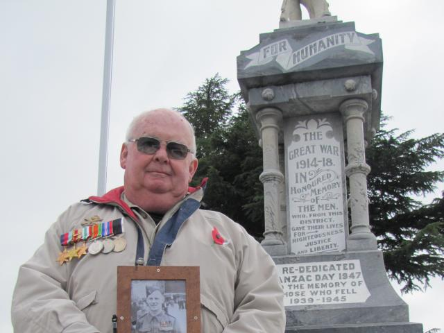 Alistair Moore, of Millers Flat, holds a photo of his late father, returned serviceman Bill Moore, during the Alexandra Anzac service yesterday. Mr Moore sen served in World War 2 in Egypt, Italy and Crete. Photo: Pam Jones.
