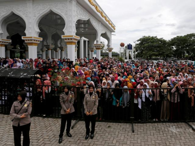 Policewomen stand guard as people watch the caning. Photo Reuters