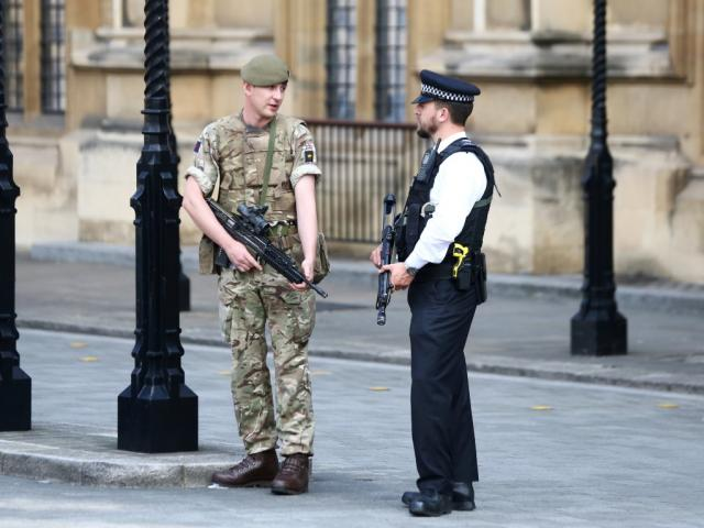 A soldier and a police officer stand guard in Westminster, London, following the attack in...