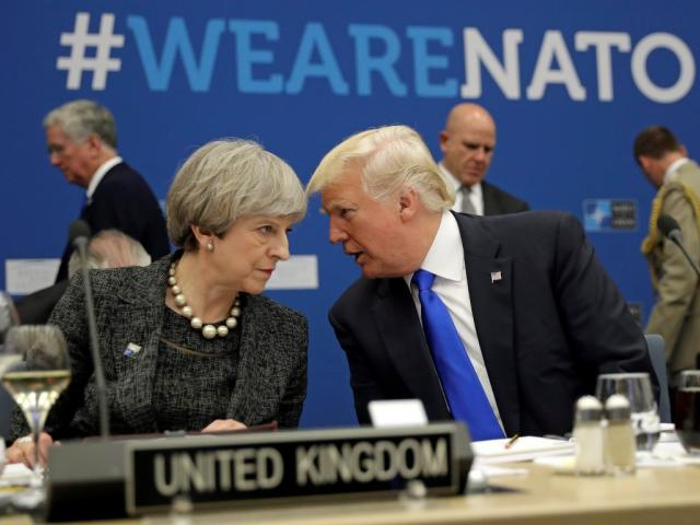 US President Donald Trump speaks to Britain's Prime Minister Theresa May during a NATO summit in...
