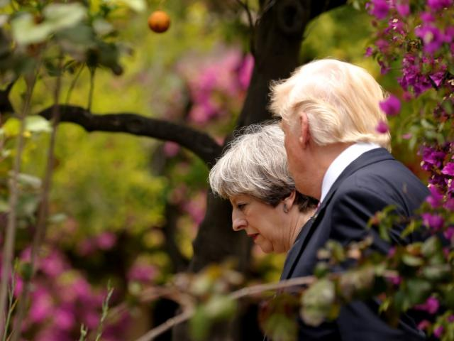 Britain's Prime Minister Theresa May talks with US President Donald Trump during the G7 Summit in...