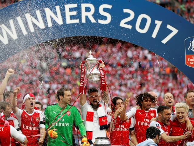 Arsenal players celebrate with the trophy at the end of the match. Photo Reuters