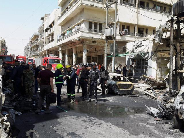 Iraqi security forces and firefighters gather at the site of car bomb attack near a government...