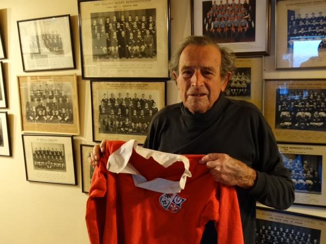 Tuppy Diack holds  Malcolm Price's 1959 Lions jersey in front of his rugby team photographs....