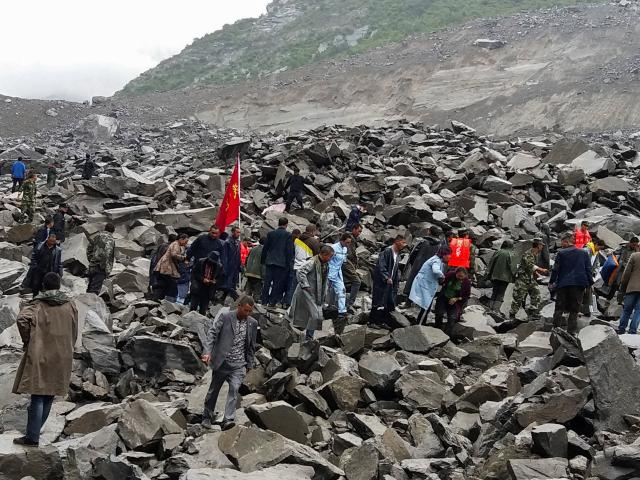 People search for survivors at the site of a landslide that destroyed some 40 households, where...