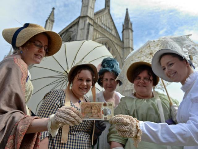 People in period costume pose with the new £10 note featuring Jane Austen. Photo: Reuters