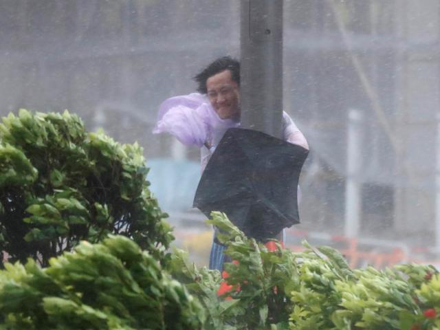A man holds on to a lamp post as Typhoon Hato hits Hong Kong. Photo Reuters