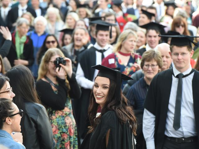 Lucy Birks (centre, 22) from Morrinsville, graduating  with a BA, reacts to friends lining the...