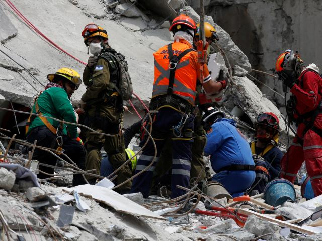 Rescue teams search for survivors in the rubble of a collapsed building in the Roma neighbourhood...
