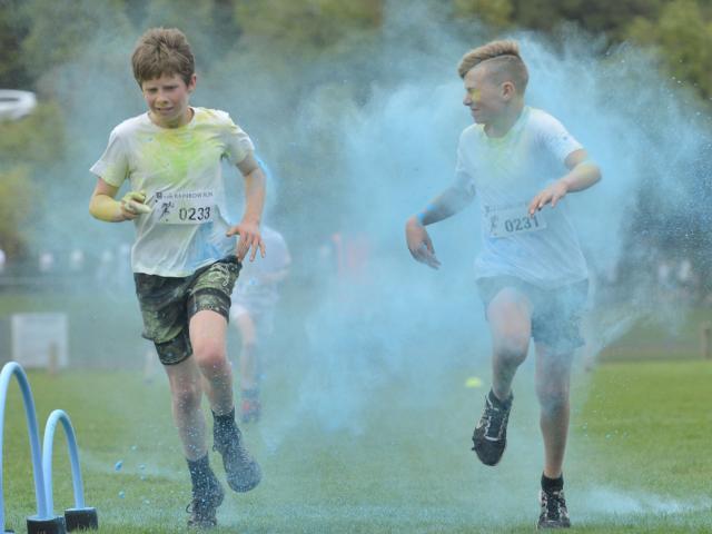 Izak Wilson (12) and Mitchell Wheeler (12), both of Dunedin, run through a cloud of blue dye on...