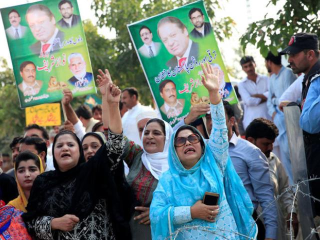 Supporters of Pakistan's former Prime Minister Nawaz Sharif chant slogans during his appearance...